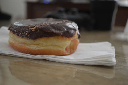 Closeup of chocolate frosted donut on a napkin Stock Photo