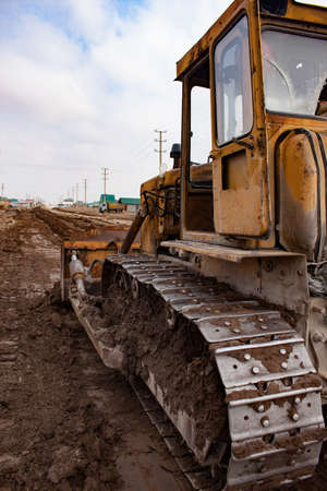 Bulldozer at work on construction site moves soil