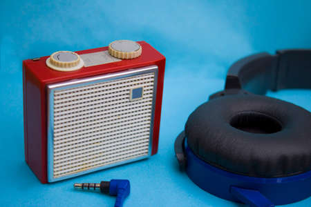 Old red radio with headphones on blue back photo