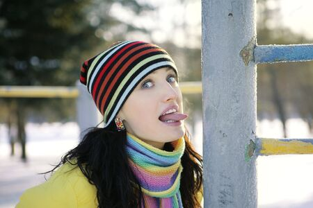 girl tongue: Girl in winter in the park language iron pipe