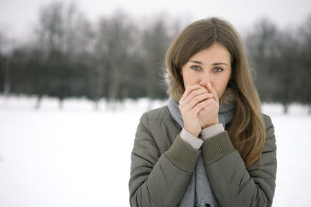 Girl in the park in winter warms the hands of breath
