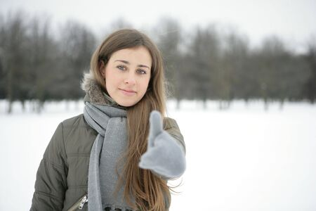 Girl in the park in winter. Hand. Sign ok photo
