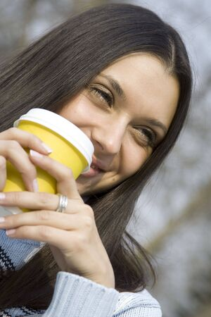 Beautiful girl in a park drinking coffee photo