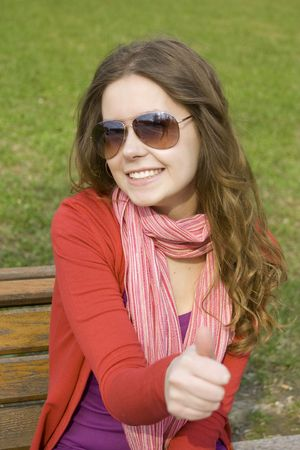 Beautiful girl in a park smiling. Thumb sign OK  photo