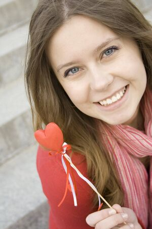 Beautiful girl with a red heart photo