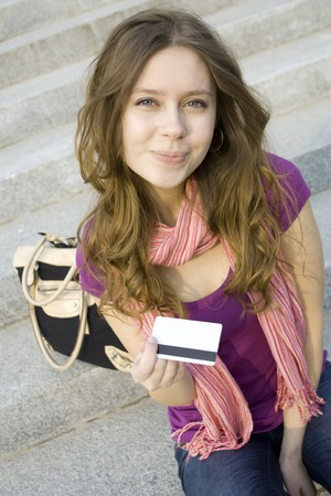 woman holds in her hand a plastic card for purchases photo