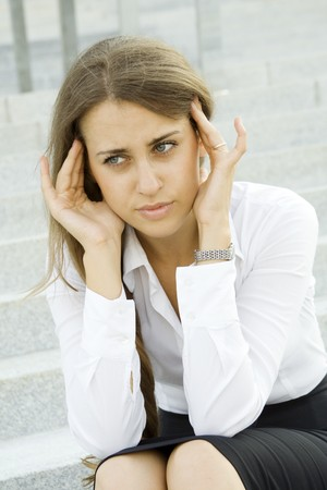 Woman tormented by headaches cares about the work