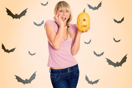 Girl terrified screams with a pumpkin for Halloween photo