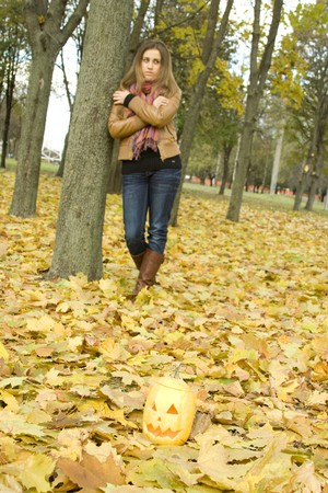 Young girl outdoors in autumn in the park with a pumpkin for Halloween photo