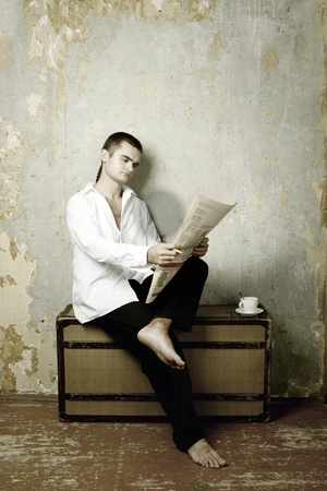Man sits on the suitcase reads the newspaper photo