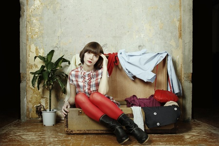 Young woman sits in a suitcase filled with clothes photo