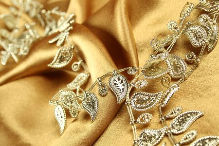 tissu or: Arri�re-plan de tissu or sur lequel r�side le bijoux or