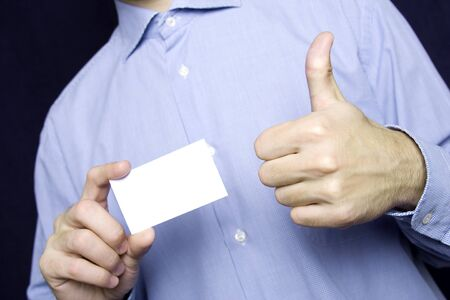 Business young man in a blue shirt holding a blank business card. Another hand the excitement thumb up photo