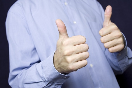 Happy young businessman in a blue shirt with a finger gesture OK photo