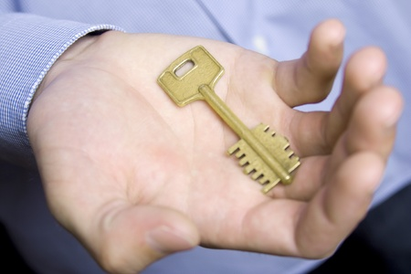Keys to the house in the palm of a young man in a blue shirt photo