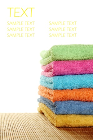 Lots of colorful bath towels stacked on each other. Isolated Stock Photo