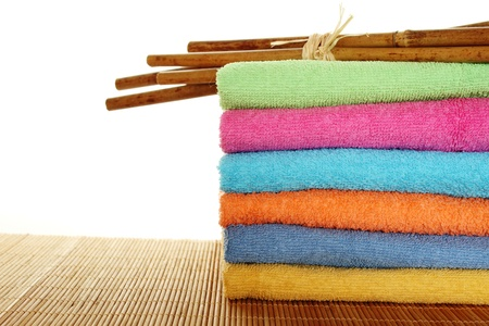 Lots of colorful bath towels stacked on each other. Side by side on a wooden surface lie bamboo sticks. Isolated photo