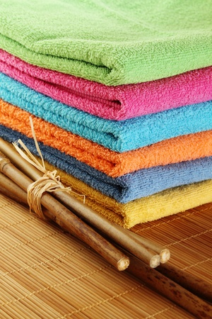 Lots of colorful bath towels stacked on each other. Side by side on a wooden surface lie bamboo sticks photo