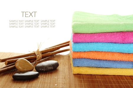 Lots of colorful bath towels stacked on each other. Side by side on a wooden surface lie bamboo sticks and stones. Isolated photo