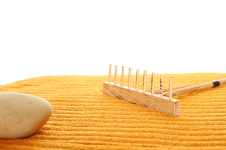 inner peace: On the golden (orange) sand with wooden rakes made strips. Beside these wooden rakes. Rake in Zen Garden taken closeup Stock Photo
