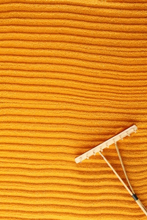 On the golden (orange) sand with wooden rakes made strips. Beside these wooden rakes. Rake in Zen Garden taken closeup Stock Photo