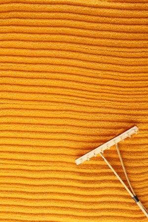 On the golden (orange) sand with wooden rakes made strips. Beside these wooden rakes. Rake in Zen Garden taken closeup Stock Photo