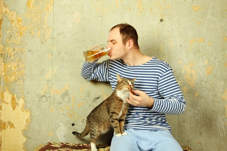 eats: Men with a beer next to the cat steals fish