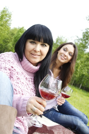 Mother and daughter drinking wine outdoors photo