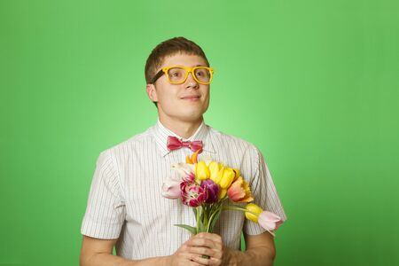 Close-up of an attractive young man in shirt bow tie and glasses holding a bouquet of tulips. Nerd photo