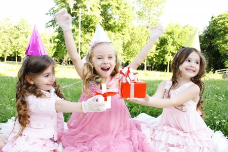 children party: Three young girls outdoors merry, celebrate a birthday, give gifts