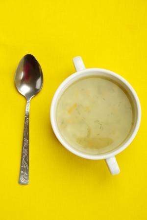 sopa de pollo: Es blanco plato de sopa sobre un fondo amarillo junto a una cuchara Foto de archivo