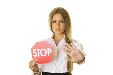 Close-up of an attractive young business woman in one hand a STOP sign, the other shows STOP gesture. isolated