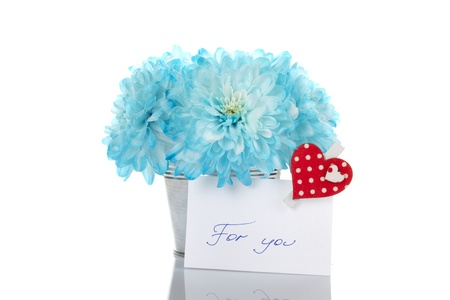 a bunch of blue flowers in a tin pot with a card photo