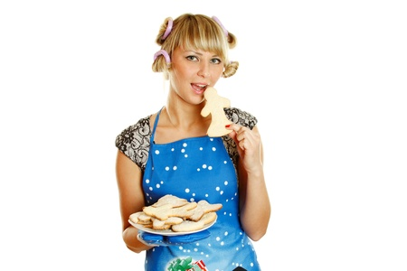 Pretty young woman in an apron and oven gloves holding a plate of gingerbread cookies for the little people christmas. Tries to bite one cookie photo