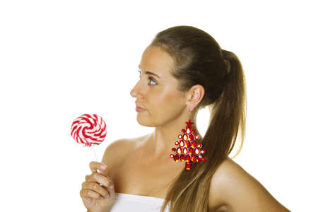 Close-up of a beautiful young woman with a lollipop and big earrings made of precious red stone in the form of a Christmas tree. Isolated photo
