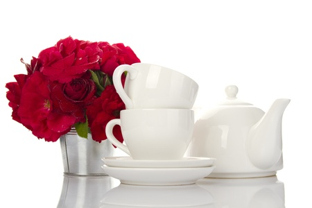 party table: White crockery for tea kettle, two cups and saucers and a bouquet of red roses in a small iron bucket