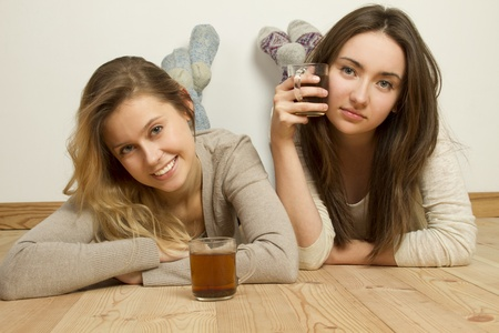 Two attractive friends drinking tea photo