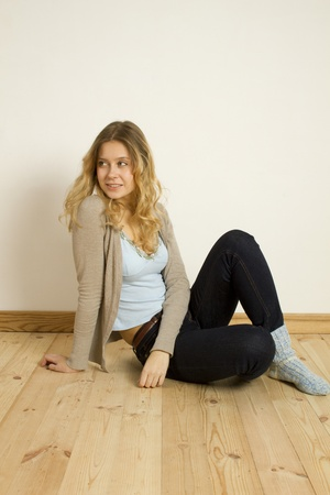 Young woman sitting on the floor at home photo