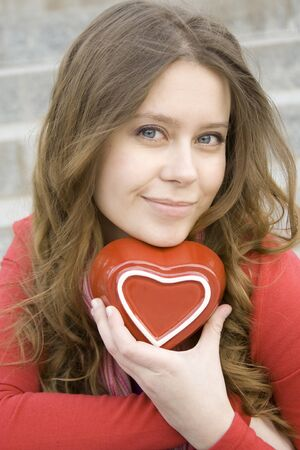 Attractive woman holding a red heart photo