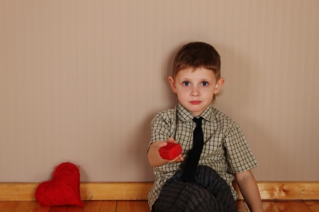 Close-up of a little boy holding a red heart photo