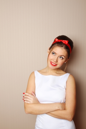 Close-up young woman in the style of 60s  White dress, red lips photo