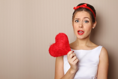 Close up of an attractive young woman holding a red heart