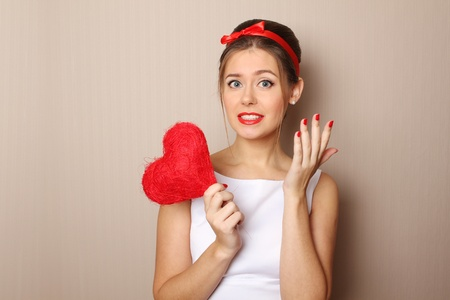 Close up of an attractive young woman holding a red heart  photo