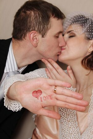 Bride and groom kissing and the hand drawn heart and says  love  photo