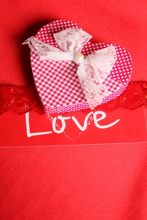 Large gift box in heart shape on red fabric  photo