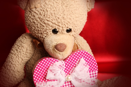 valentine s day teddy bear: Close up of a teddy bear holding a big gift box as heart