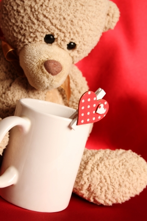 Teddy bear with a big white cup of tea and a red heart Stock Photo