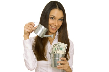 bucket of money: Business woman holding money in a bucket  Isolated