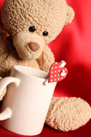 Teddy bear with a big white cup of tea and a red heart photo
