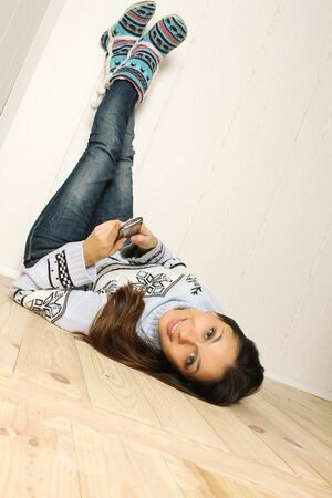 Young woman lying at home with a mobile phone photo